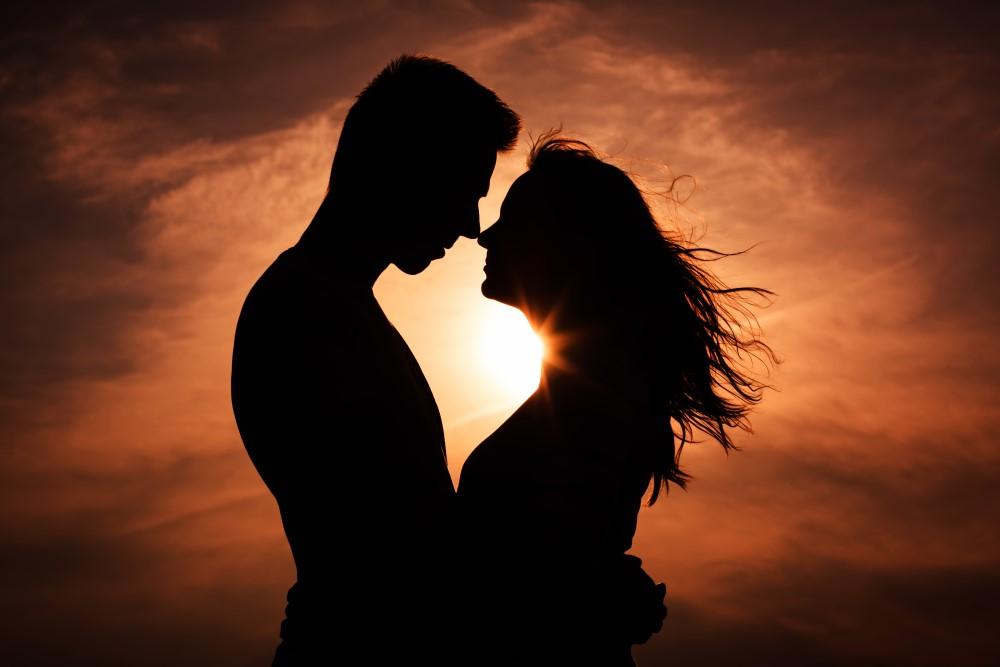 Romantisk par der er på kærestetur og nyder en solnedgang sammen